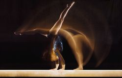 Female Gymnast In Motion. Multiple exposure image of female gymnast in motion on balance beam Royalty Free Stock Photo