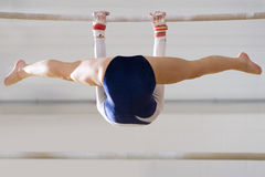 Female gymnast performing on bar, low angle view royalty free stock photos