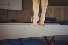 Female gymnast practicing gymnastics on the balance beam royalty free stock photo