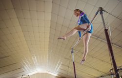 Female gymnast practicing gymnastics on the horizontal bar stock image
