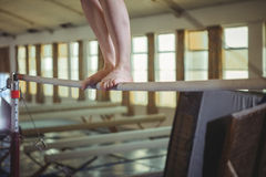 Female gymnast practicing gymnastics on the horizontal bar royalty free stock photo
