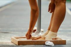 Free Female Gymnast Rubs Chalk On His Legs Stock Image - 118420681
