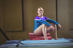 Female gymnast sitting on big wedge in the gymnasium stock image