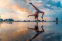 Female gymnast standing on one hand and keeping balance during dramatic sunset with reflection in the water of amazing