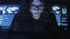 Bespectacled woman hacker programmer is working on computer in cyber security center filled with display screens. Binary. Female hacker programmer is working on stock video footage
