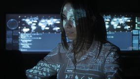 Woman Hacker programmer is working on computer in cyber security center filled with display screens. Binary code on her. Female Hacker programmer is working on stock footage