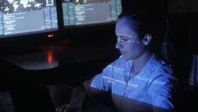 Woman Hacker programmer is working on computer in cyber security center filled with display screens. Binary code on her. Female Hacker programmer is working on stock video footage