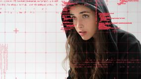 Female hacker using a laptop. Digital composite of a young Caucasian female hacker wearing a hood while using a laptop and foreground shows codes stock video footage