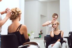 Female hair stylist braids her beautiful client's hair at the beauty salon stock photography