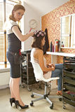 Female hairdresser adjusting curlers in young woman's hair Stock Image