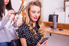 Female hairdresser applying hair straightener for long hair of smiling young woman Royalty Free Stock Images