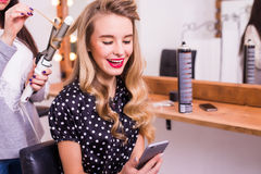 Female hairdresser applying hair straightener for long hair of smiling young woman Stock Images