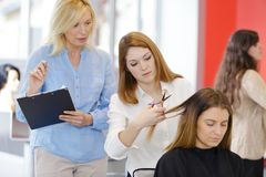 Female hairdresser apprentice during training. Woman stock photos