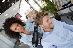 Female hairdresser blow drying male clients hair. Hairdresser stock photography