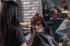 Female hairdresser brushing and drying using hand held blow drye. R on hair of young brunette women while she is sitting in armchair in beauty salon Stock Photos