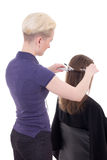 Female hairdresser curling hair to client isolated on white Stock Image