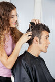 Female Hairdresser Cutting Client's Hair Stock Photo