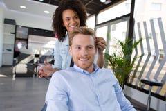 Female hairdresser cutting hair bearded man client Stock Photos