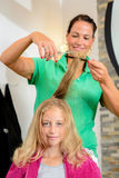 Female hairdresser cutting hair of blond girl. In her shop royalty free stock images