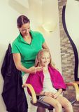 Female hairdresser cutting hair of blond girl. In her shop royalty free stock photos