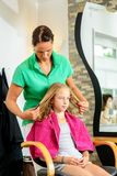 Female hairdresser cutting hair of blond girl. In her shop stock photography