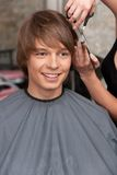 Female hairdresser cutting hair of man client. Royalty Free Stock Images