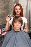 Female hairdresser cutting hair of man client and looking into camera. Stock Photography