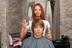 Female hairdresser cutting hair of man client and looking into camera. Royalty Free Stock Photography
