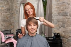 Female hairdresser cutting hair of man client and smiling. Stock Photo
