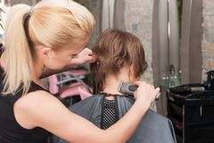 Female hairdresser cutting hair of man client using trimmer Stock Images