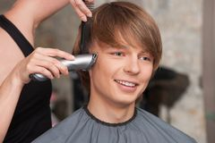 Female hairdresser cutting hair of man client using trimmer. Royalty Free Stock Image