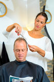 Female hairdresser cutting hair of man Royalty Free Stock Photos
