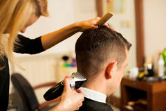 Female hairdresser cutting hair of smiling man client at beauty Stock Photos