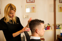 Female hairdresser cutting hair of smiling man client at beauty Royalty Free Stock Images