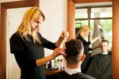 Female hairdresser cutting hair of smiling man client at beauty Stock Photography