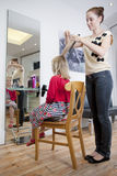 A female hairdresser cutting a young girls hair in a hairdressing salon Royalty Free Stock Photography
