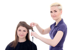 Female hairdresser doing haircut to young beautiful woman isolat Stock Images