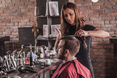 Female hairdresser hairstyle hair of man in chair Royalty Free Stock Photo