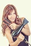 Female hairdresser holding hairdryer and brush Stock Photography