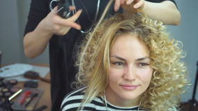 Female hairdresser making hairstyle to blonde girl in beauty salon. stylist makes African curls in a beauty salon. stock footage