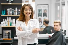 Female hairdresser posing in front of young male client. royalty free stock photos
