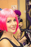 Female hairdresser at the salon with pink wig on her head Stock Image