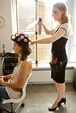 Female hairdresser spraying hairspray in customer's hair Royalty Free Stock Photography