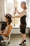 Female hairdresser spraying hairspray in customer's hair Royalty Free Stock Photography