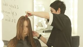 Female hairdresser spraying water on hair during cutting in hairdressing salon. Close up hairdresser making female stock video footage