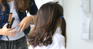 Female hairdresser standing and making hairstyle to cute lovely young asian teen in beauty salon stock video footage