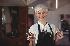 Female hairdresser standing with scissor and comb at a salon Stock Photo