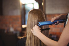 Female hairdresser straightening the hair of a client Royalty Free Stock Images