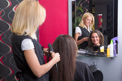 Female hairdresser straightening woman's hair in beauty salon Royalty Free Stock Image