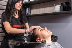 Female hairdresser wiping off the remains of paint with a cotton. Disc from the head of women after washing her hair in washing sink in beauty salon Stock Photo